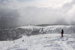 Esquiador nas montanhas, no piste preparado e no dia ensolarado foto de stock