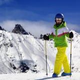 Esquiador novo com os polos de esqui em montanhas nevado no dia de inverno do sol imagem de stock
