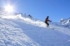 Esquiador que apresura abajo de la montaña en un día soleado en España Imagenes de archivo