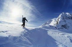 Esquiador que camina a la cumbre de la montaña Imágenes de archivo libres de regalías