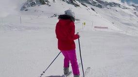 Esquiador que esquía abajo en cuesta de montaña en invierno y esquís del freno para parar almacen de metraje de vídeo