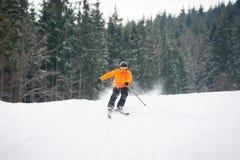 esquiador que esquía cuesta abajo después de salto de altura en la estación de esquí Imágenes de archivo libres de regalías