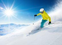 Esquiador que esquía cuesta abajo en altas montañas foto de archivo libre de regalías
