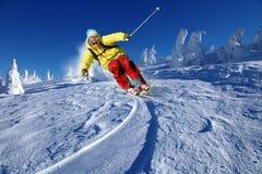 Esquiador que esquía cuesta abajo en altas montañas Imagen de archivo