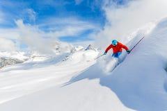 Esquiador que esquía cuesta abajo en altas montañas Fotografía de archivo