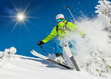 Esquiador que esquía cuesta abajo en altas montañas Imagenes de archivo