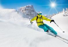 Esquiador que esquía cuesta abajo en altas montañas Imagen de archivo libre de regalías