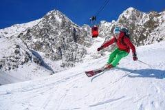Esquiador que esquía cuesta abajo en altas montañas contra la elevación del cable Fotografía de archivo libre de regalías