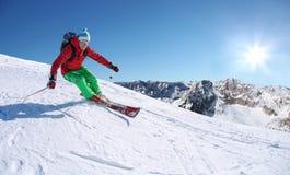 Esquiador que esquía cuesta abajo en altas montañas contra la elevación del cable Imagen de archivo libre de regalías