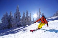 Esquiador que esquía cuesta abajo en altas montañas contra puesta del sol Imágenes de archivo libres de regalías