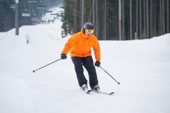Esquiador que esquía cuesta abajo en la estación de esquí contra el funicular Foto de archivo libre de regalías