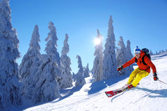 Esquiador que esquía cuesta abajo en altas montañas contra puesta del sol Imagen de archivo