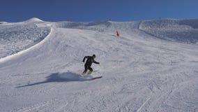 Esquiador que esquia abaixo da inclinação, girando certo e à esquerda rapidamente, freios com a neve do pulverizador filme