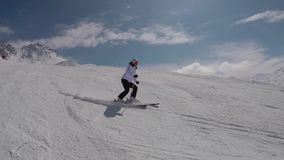 Esquiador que esquia abaixo de A que cinzela das inclinações de montanha no inverno no esqui em declive filme