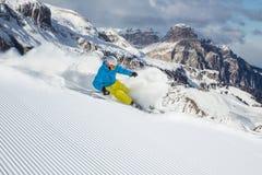 Esquiador que esquia para baixo nas montanhas altas Fotos de Stock