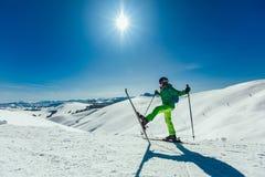 Esquiador que está com um pé levantado em uma inclinação do esqui em um dia ensolarado imagens de stock