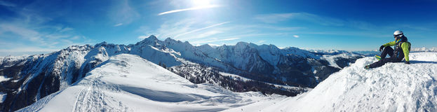 Esquiador que se sienta encima de una montaña foto de archivo libre de regalías