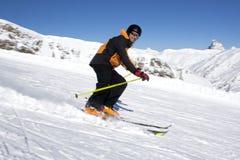 Esquiador que sonríe mientras que va abajo de la colina Imágenes de archivo libres de regalías
