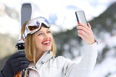 Esquiador que toma un selfie con un smartphone Fotos de archivo