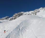 Esquiador solitario que elude encima de cuesta del esquí Imagenes de archivo