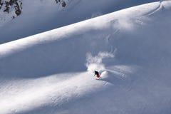 Esquiador solitario a solas que pone primeras pistas en el suelo frescas en la montaña Fotos de archivo libres de regalías