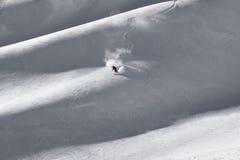Esquiador solitario a solas que pone primeras pistas en el suelo frescas en ridg de la montaña Fotografía de archivo libre de regalías