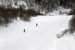 Esquiador y snowboarder cuesta abajo en cuesta del esquí en el día de invierno gris Foto de archivo