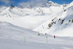 Esquiador y snowboarder cuesta abajo en rastro y las montañas del freeride i Imagenes de archivo