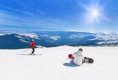 Esquiador y snowboarder que esquían cuesta abajo en las montañas, deporte de invierno Imagen de archivo