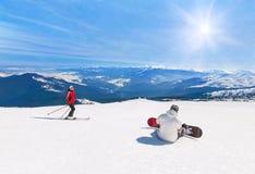 Esquiador y snowboarder que esquían cuesta abajo en las montañas, deporte de invierno Imágenes de archivo libres de regalías