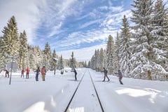 Esquiadores a campo través que pasan la pista de ferrocarril Imagenes de archivo