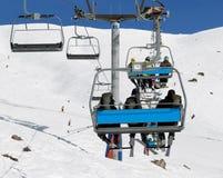 Esquiadores con las mochilas en la telesilla Fotografía de archivo