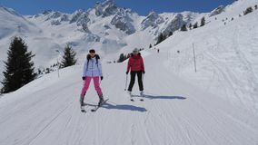 Esquiadores da mulher do retrato dois que esquiam abaixo da inclinação ideal da montanha no inverno filme