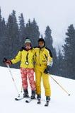 Esquiadores de los pares bajo nevadas Imagen de archivo