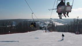 Esquiadores e snouborders em um elevador de esqui pov no tempo de inverno O teleférico levanta os povos até a inclinação vídeos de arquivo