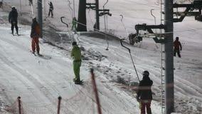 Esquiadores e snowboarders em um elevador de esqui filme
