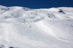 Esquiadores em inclinações do esqui em alpes franceses Foto de Stock Royalty Free