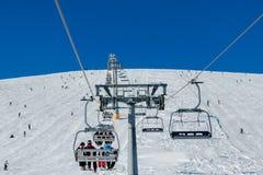 Esquiadores em um elevador e em uma pista de esqui Fotografia de Stock Royalty Free