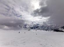 Esquiadores en cuesta del esquí antes de la lluvia Imagenes de archivo