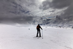 Esquiadores en cuesta del esquí antes de la tormenta Imagen de archivo libre de regalías