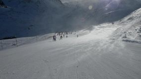 Esquiadores en el piste que entra cuesta abajo en fuertes vientos almacen de video