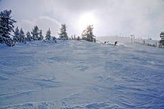Esquiadores en la cuesta en el centro turístico del invierno fotos de archivo