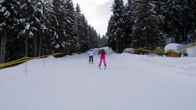 Esquiadores felizes das mulheres que esquiam em Forest Slope In The Mountain e nos braços dos aumentos acima video estoque