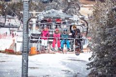 Esquiadores na estância de esqui em um fundo dos esqui-elevadores, florestas, Fotografia de Stock