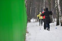 Esquiadores que corren en la madera de la nieve fotografía de archivo