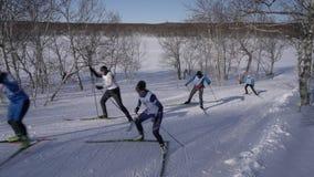 Esquiadores que corren a lo largo de pista del esquí en bosque del invierno el día soleado almacen de metraje de vídeo