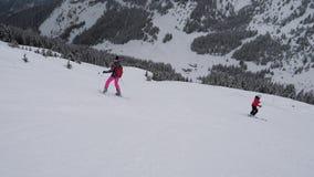 Esquiadores que esquiam na montanha da dificuldade para baixo em feriados de inverno video estoque