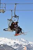Esquiadores que suben con una elevación de esquí Fotografía de archivo