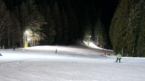 Esquiadores que têm o esqui do divertimento na trilha da inclinação da noite vídeos de arquivo