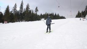 Esquiadores que usan el ancla del remonte en la montaña Gente que mueve lentamente ascendente en la elevación de la fricción e almacen de video